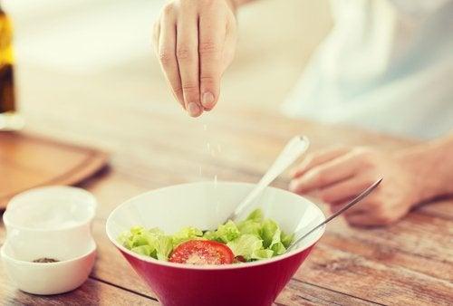 Uomo che mette sale in insalata