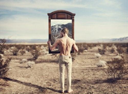 Uomo regge specchio rotto