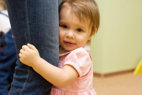 Bambina si nasconde dietro la gamba della madre