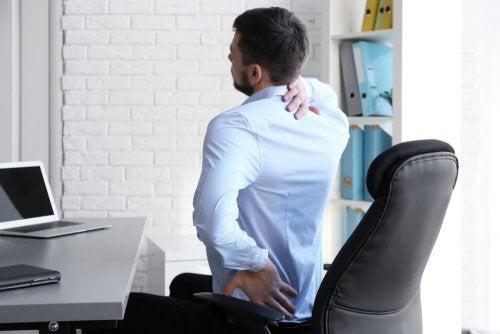 Uomo al pc con mal di schiena
