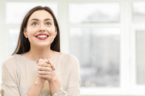 Donna felice con le mani giunte