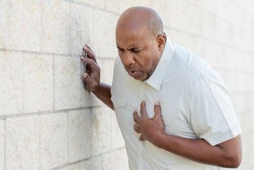 Emergenza cardiaca: uomo si stringe il petto.