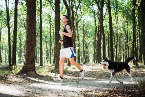 ragazzo che corre nel bosco con il cane