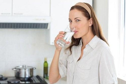 Donna che beve acqua per espellere i calcoli renali.