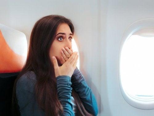 Donna in aereo che fa respiri profondi per trattenere vomito