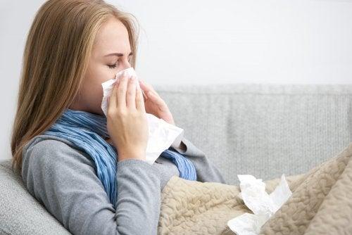 Donna sul divano con raffreddore