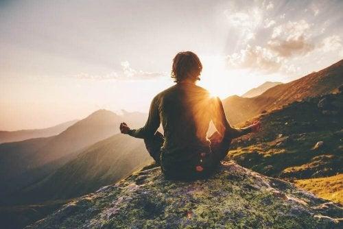 Ragazzo che medita in montagna