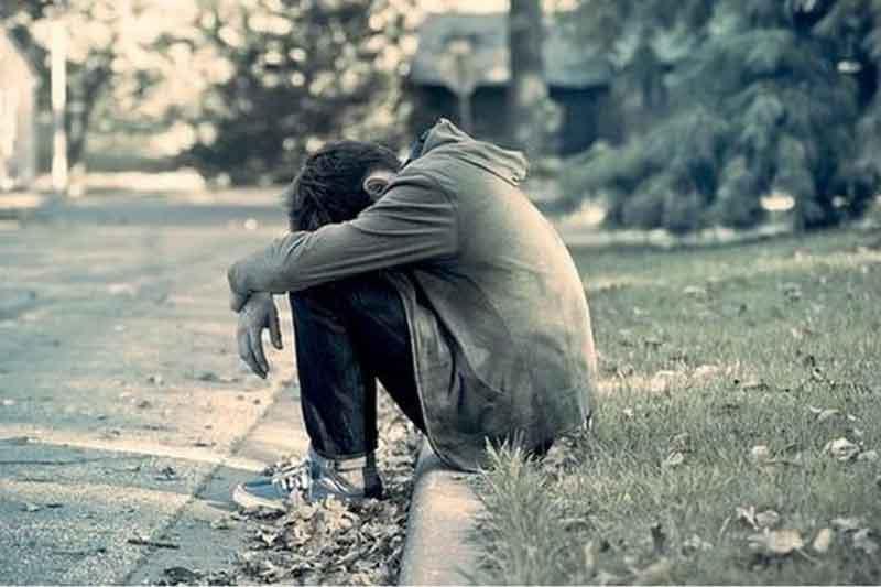 Ragazzo triste seduto sul ciglio della strada