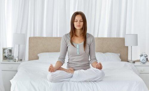Ragazza medita a letto prima di dormire