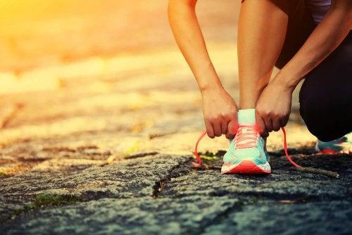 donna si allaccia scarpe da ginnastica