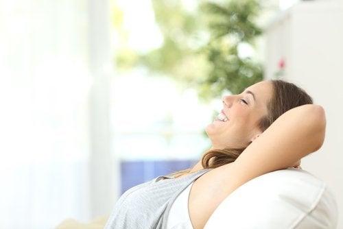 Donna sorridente si rilassa sul divano