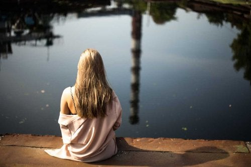 Ragazza seduta davanti a lago