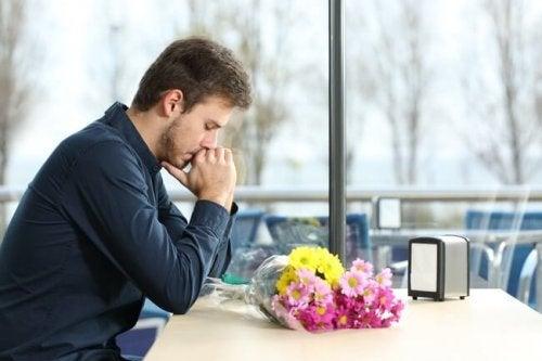 Uomo pensieroso con mazzo di fiori