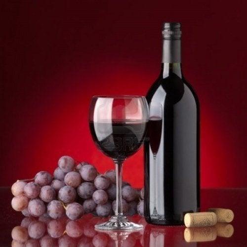 bottiglia e bicchiere di vino rosso e uva