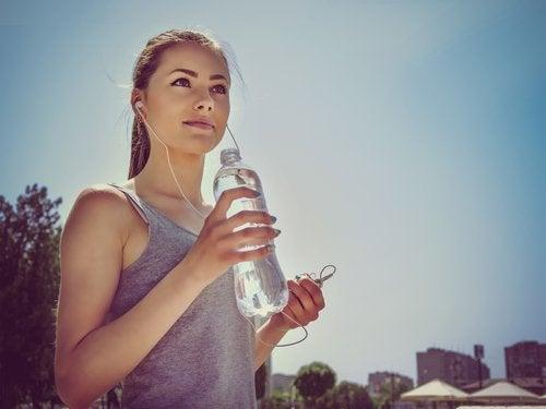 Ragazza con cuffie e bottiglia acqua