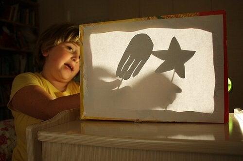 bambino proietta figure al buio
