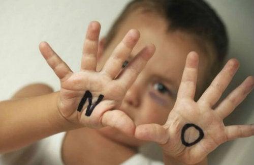 Bambino con scritta No sulle mani