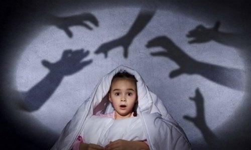 bambina sotto le coperte e mani immaginarie sopra di lei