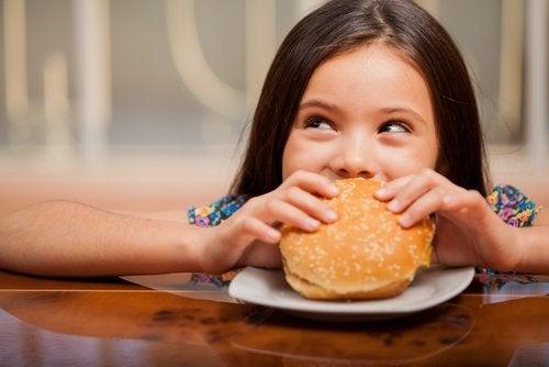 Bambina mangia hamburger