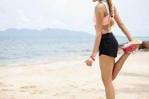 donna fa stretching in spiaggia