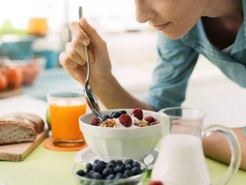 Donna che mangia yogurt con frutti rossi