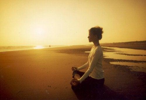 Donna che medita sulla spiaggia