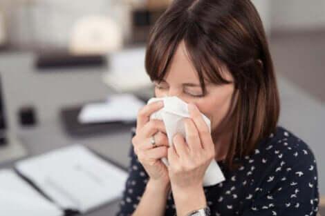 Propoli contro i sintomi di raffreddore e influenza: donna che si soffia il naso.