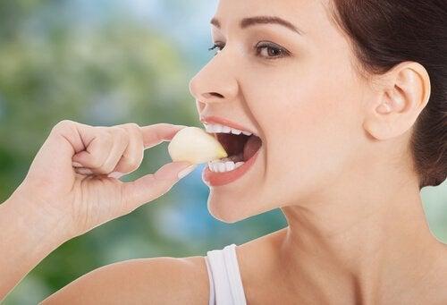 donna mangia spicchio di aglio intero