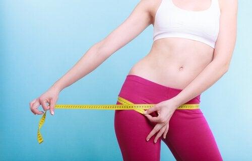Donna con un metro mer misurare il suo corpo e scoprirne la forma