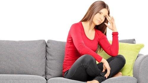 Anomalie del ciclo mestruale - Donna pensierosa sul divano