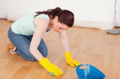 Donna con guanti cerca di eliminare graffi dal pavimento
