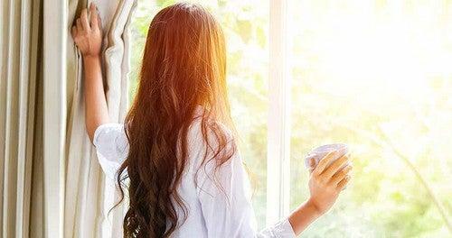 Donna si affaccia alla finestra.