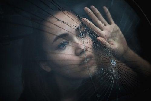 Donna con mano appoggiata su vetro rotto