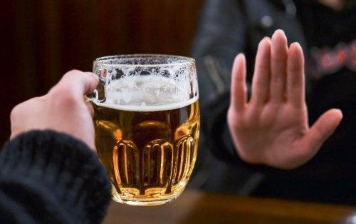persona dice no con la mano a bicchiere di birra