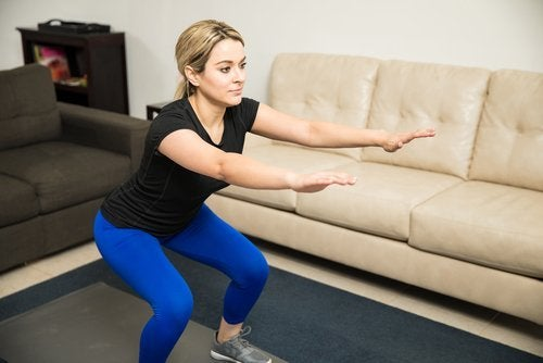 Esercizi di squat eseguiti da donna in salotto