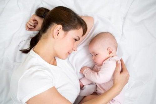 Neonato con madre sul letto