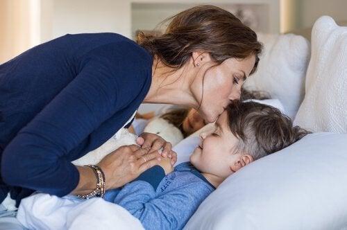 Mamma che dà il bacio della buonanotte ai figli