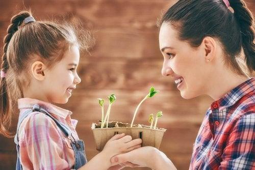Mamma e figlia che tengono una piantina