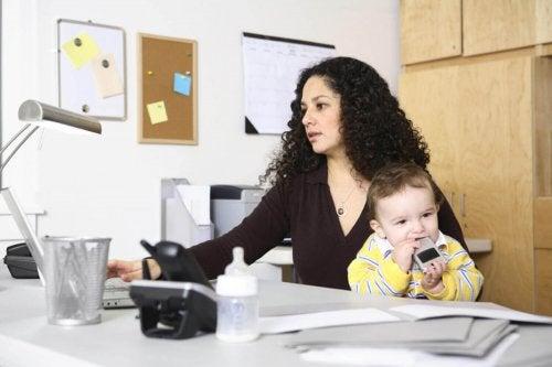 Mamma che lavora mentre tiene il suo bambino essere una super mamma