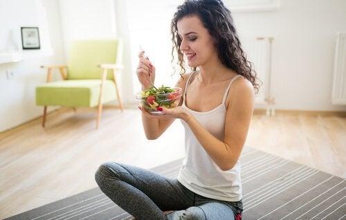 ragazza seduta che mangia insalata