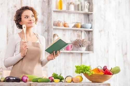 donna in cucina con libro di ricette e verdure