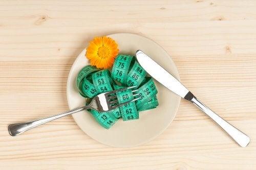 piatto con metro fiore forchetta e coltello