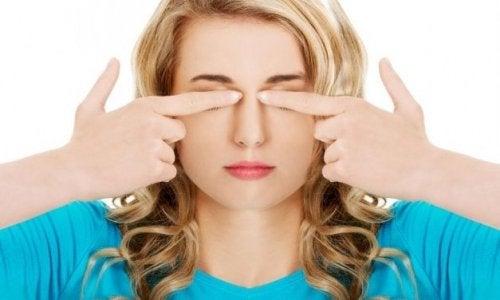 donna esercita pressione sulle palpebre
