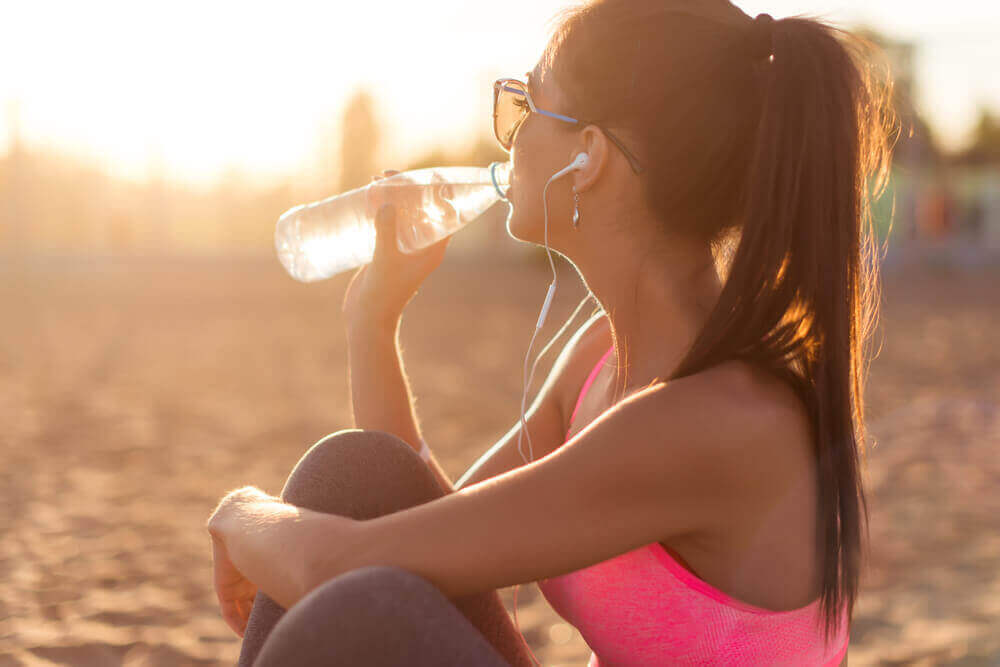 Ragazza beve acqua da una bottiglia