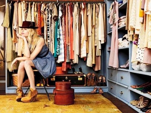 Guardaroba con vestiti e ragazza seduta