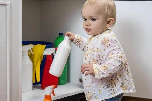 Bambina che prende una bottiglia di candeggina