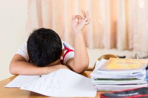 Niño cansado con la cabeza en los libros