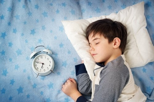 Niño durmiendo sereno con reloj despertador al lado