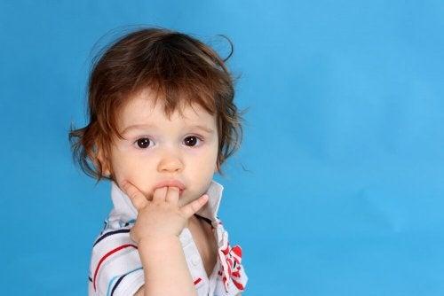 Bambino con le dita in bocca che continua a succhiarsi il pollice