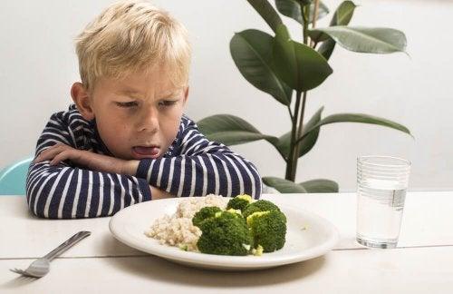 Bambino disgustato davanti a un piatto di verdure